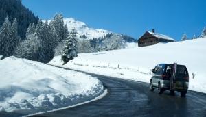 Mini van équipé pour la neige sur une route de montagne